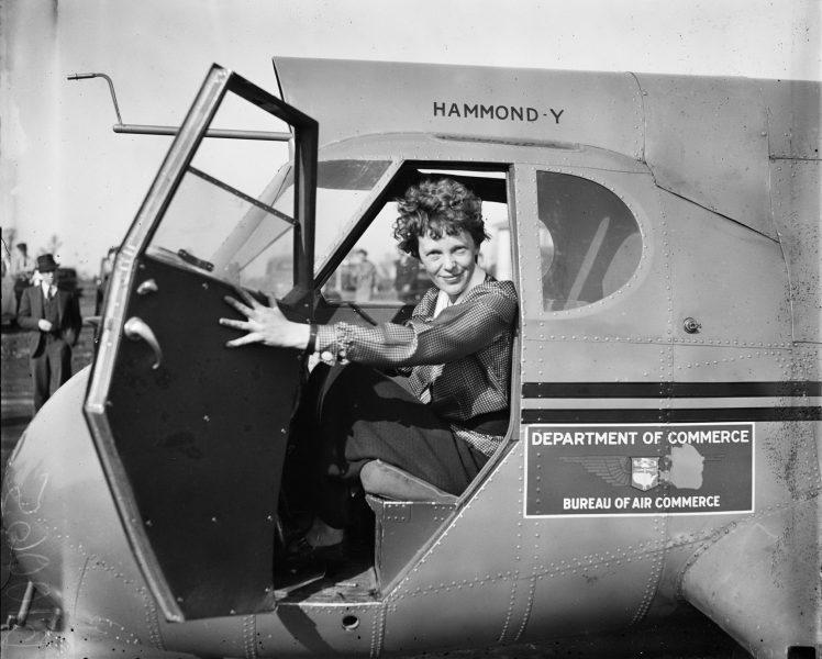 Amelia Earhart on her plane - Amelia Earhart Facts For Kids