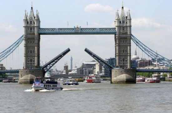 Bascules of Tower Bridge are raised allowing vessel to pass